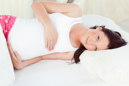 Young pregnant woman resting in her bed in the bedroom photo