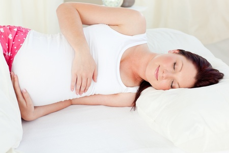 Radiant pregnant woman sleeping in her bed photo