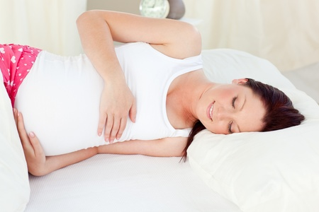 Smiling pregnant woman resting in her bed in the bedroom photo