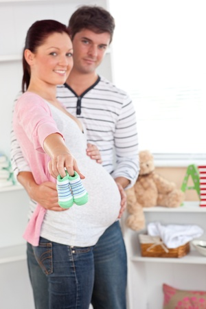 Cheerful pregnant woman holding baby shoes while husband touching her belly in the room of their fut photo