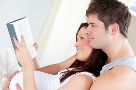Close-up of a pregnant woman and her husband reading a book on the sofa photo