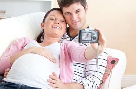Close-up of a cheerful pregnant woman and her husband taking pictures of themselves on a sofa photo