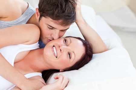 smooch: Caring caucasian couple lying on bed in the bedroom Stock Photo