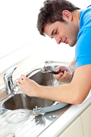 Caucasian man repairing a kitchen sink at home photo