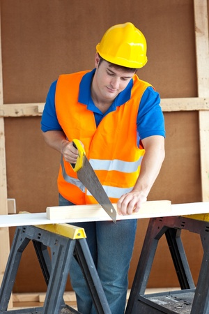 Handsome male worker wearing a yellow hardhat sawing a wooden board photo