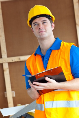 Thoughtful male worker holding a clipboard photo