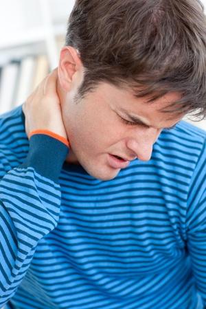body pain: Caucasian man having a neckache in the living-room