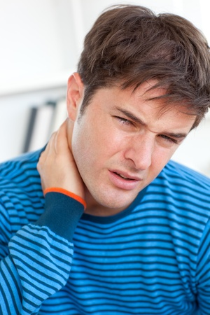 Young caucasian man having a neckache in the living-room photo