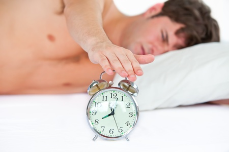 Asleep young man stopping his ringing alarm clock in the bedroom photo