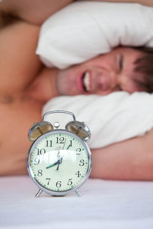 waking: Angry young man lying in bed and annoyed by his alarm clock in the bedroom