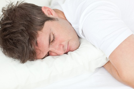 Young caucasian man sleeping in his bed photo