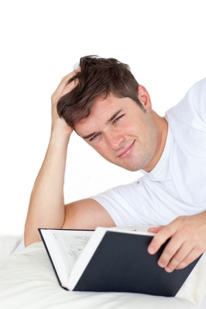 Smiling man reading a book lying on his bed photo