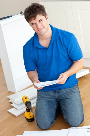 manual: Charismatic young man reading the instructions to assemble furniture in the kitchen Stock Photo