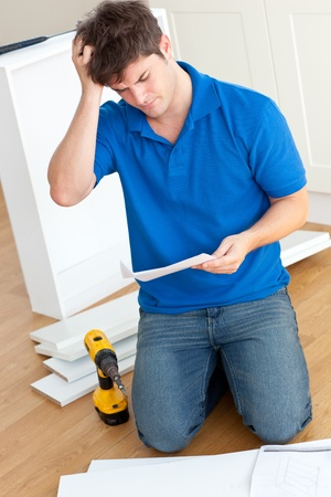 Incomprehensive young man reading the instructions to assemble furniture in the kitchen photo