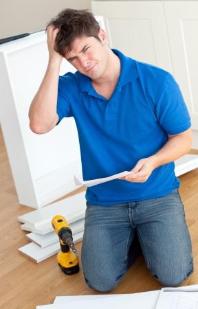 instructions: Incomprehensive caucasico uomo che legge le istruzioni per il montaggio mobili in cucina