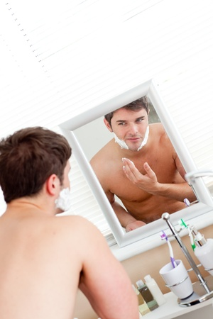Good-looking caucasian man ready to shave in the bathroom photo