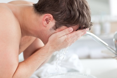 midlife: Cute caucasian man spraying water on his face after shaving in the bathroom