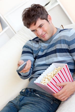 http://us.123rf.com/450wm/wavebreakmediamicro/wavebreakmediamicro1108/wavebreakmediamicro110850504/10244487-delighted-young-man-eating-popcorn-and-holding-a-remote-lying-on-the-sofa.jpg