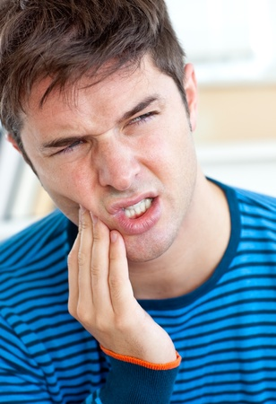 downcast: Unhappy caucasian man having a toothache in the living-room