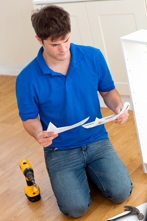 Concentrated young man reading the instructions to assemble furniture in the kitchen Stock Photo - 10244040
