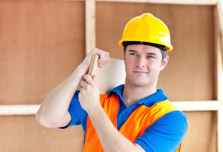 assertive: Assertive young male worker with a yellow helmet carrying a wooden board