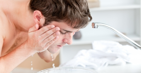 shaving blade: Young caucasian man spraying water on his face after shaving in the bathroom Stock Photo