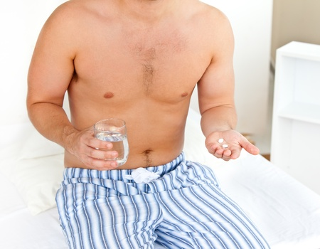 Depressed young man sitting on his bed and holding a glass of water and pills in his bedroom photo