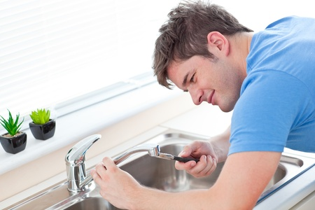 home repair: Self-assured man repairing his sink in the kitchen Stock Photo