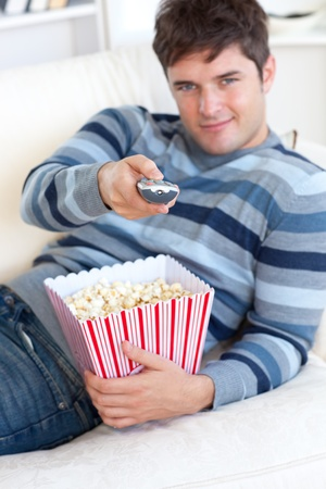 Relaxed young man eating popcorn and holding a remote lying on the sofa photo