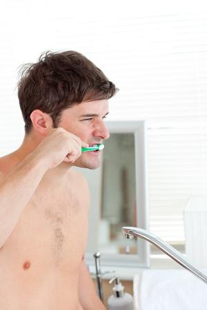 Good-looking young man brushing his teeth in the bathroom photo