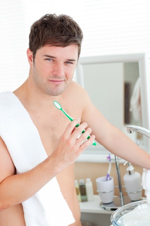 Positive young man with a towel brushing his teeth in the bathroom photo