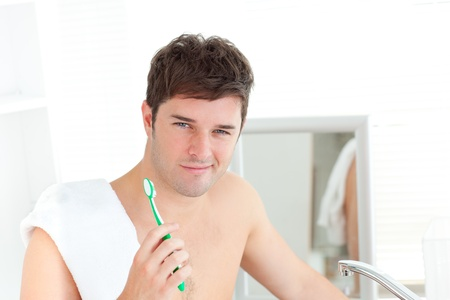 Smiling young man with a towel brushing his teeth in the bathroom photo