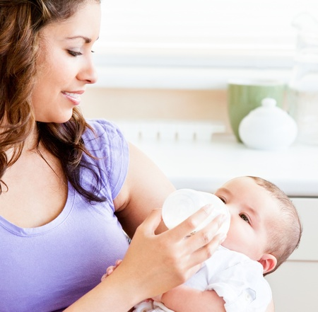 radiant: Radiant mother feeding her adorable son in the kitchen Stock Photo