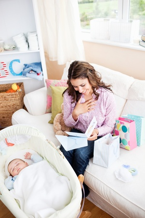 Bright woman sitting on the sofa with bags reading a card while her baby is sleeping in his cradle photo