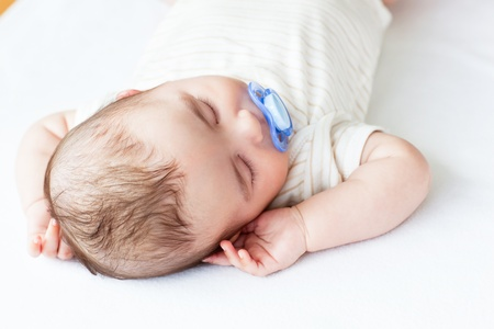 Portrait of an adorable baby with a pacifier sleeping in a bed photo