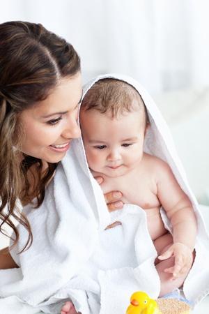 madre y bebe: Madre encantada secado a su bebé después de su baño Foto de archivo