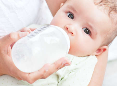 baby bottle: Charming mother feeding her adorable son in the kitchen Stock Photo