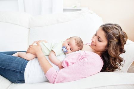 madre y bebe: Joven madre cuidar de su beb� adorable Foto de archivo