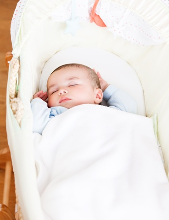 Close-up of an adorable baby sleeping in his cradle photo