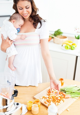 Radiant mother preparing food for her adorable baby in the kitchen photo