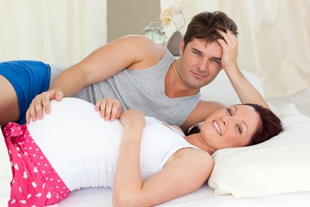 Happy caucasian pregnant woman lying on bed with her husband photo