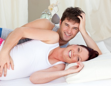 Laughing caucasian pregnant woman lying on bed with her husband photo