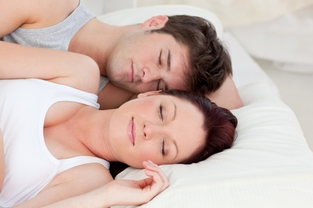 Enamored young couple sleeping in bed together photo