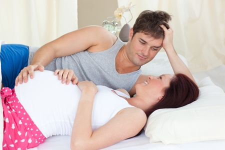 Delighted caucasian pregnant woman lying on bed with her husband photo