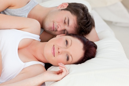 Bright caucasian couple lying on bed photo
