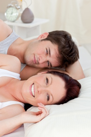 Positive caucasian couple lying on bed photo