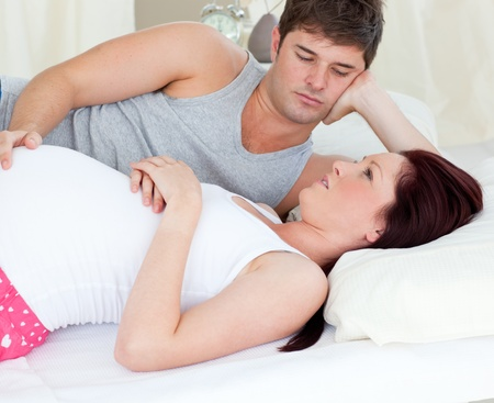 Worried pregnant woman lying on bed with her husband photo