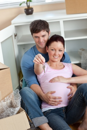 Delighted couple expecting a baby sitting on the floor and holding the key of their new house photo