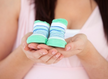 homme enceinte: Gros plan sur une femme enceinte tenant chaussures de b�b�