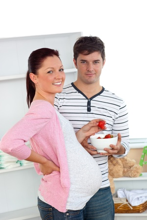 Portrait of a smiling pregnant woman eating strawberries and of her husband photo